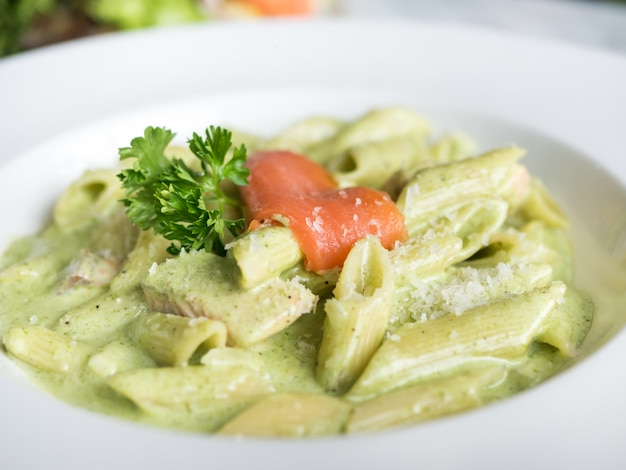 Traditional italian penne pasta with pesto sauce and salmon.