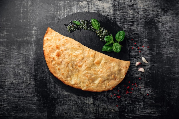 Traditional italian pizza calzone with ingredients on a stone and dark wooden scratched background
