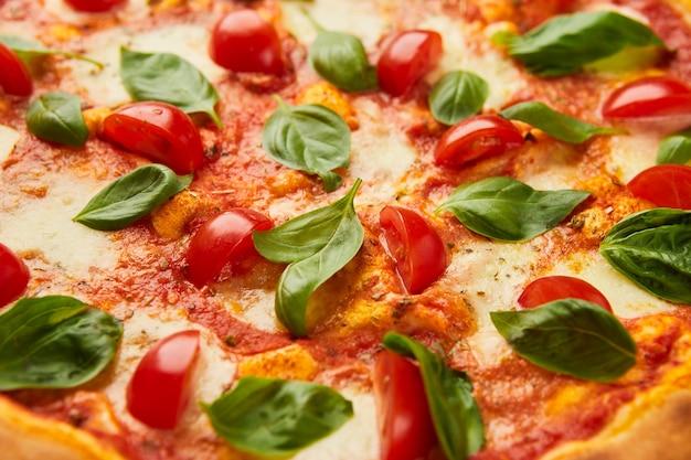 緑の草の上にチーズ、トマト、バジルを添えた伝統的なイタリアンピザマルガリータ