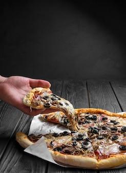 濃い黒の木の板に伝統的なイタリアンピザ、手にピザ、