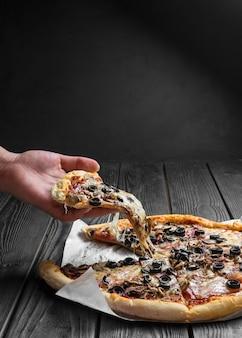짙은 검은색 나무 판자 위에 있는 전통적인 이탈리아 피자, 손에 피자 한 조각,