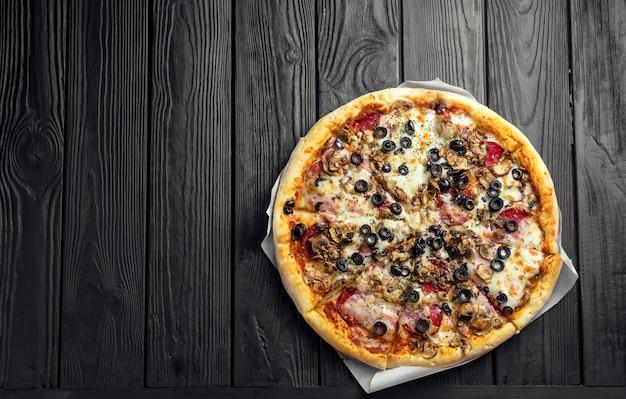 暗い黒い木の板、トップビューで伝統的なイタリアのピザ