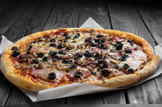 짙은 검은색 나무 판자에 있는 전통적인 이탈리아 피자