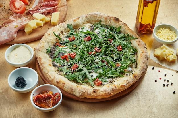 Традиционная итальянская пицца с рукколой, моцареллой, трюфелем и вялеными помидорами на деревянный стол. высокий пропуск на пост