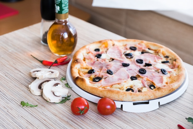 Traditional italian pizza with ham and olives