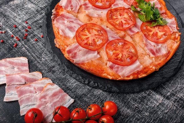 Traditional italian pizza with mozzarella cheese, ham, tomatoes, pepper, pepperoni spices and fresh rucola
