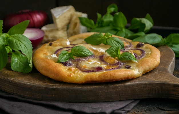 Traditional italian pizza with onion and basil.