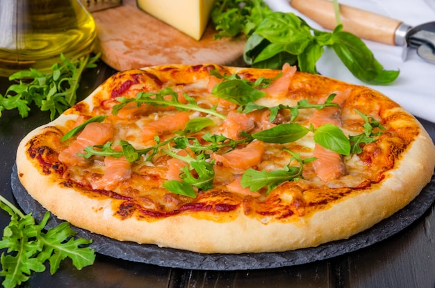 Traditional italian pizza with tomato sauce, smoked salmon and fresh arugula on a dark stone.