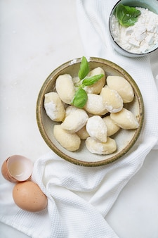 バジルの葉、卵、小麦粉で飾られた伝統的なイタリアのジャガイモのニョッキ。上面図。フラットレイ
