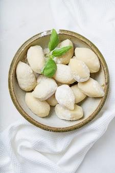 バジルの葉で飾られた伝統的なイタリアのジャガイモのニョッキ。上面図。フラットレイ