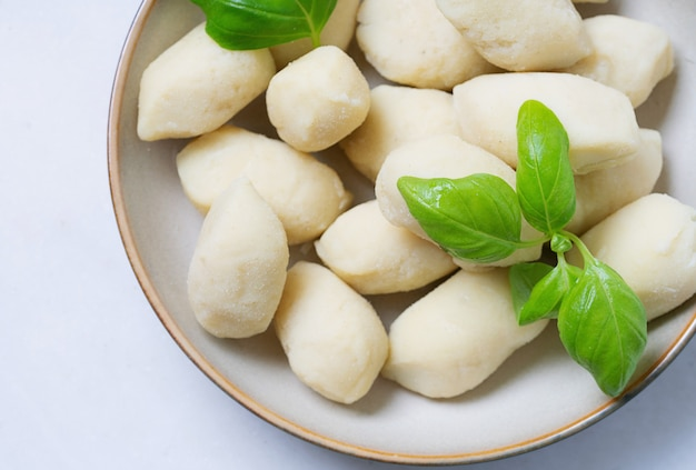 Traditional italian potato gnocci  (pasta) decorated with basil leaf, in ceramic plate. uncooked pasta concept. top view. flat lay