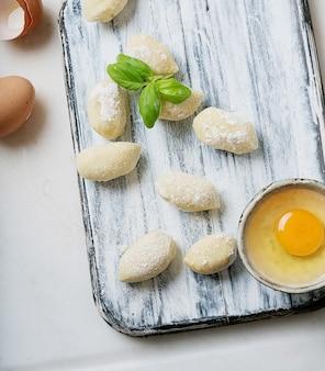 バジルの葉、卵、小麦粉で飾られた伝統的なイタリアのジャガイモのニョッキ(パスタ)。未調理のパスタのコンセプト。上面図。フラットレイ