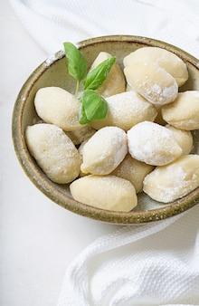 バジルの葉、卵、小麦粉で飾られた伝統的なイタリアのジャガイモのニョッキ(パスタ)。未調理のパスタのコンセプト。