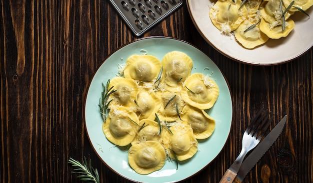 ローズマリーとパルメザンチーズを添えた伝統的なイタリアのラビオリを素朴な木製のテーブルでお召し上がりいただけます。イタリアのパスタ。上面図、コピースペース