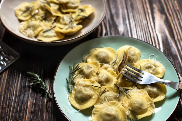 ローズマリーとパルメザンチーズを添えた伝統的なイタリアのラビオリを素朴な木製のテーブルでお召し上がりいただけます。イタリアのパスタ