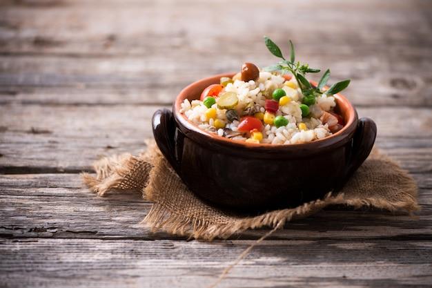 Традиционный итальянский рисовый салат на деревянном столе