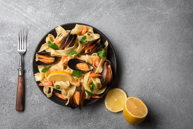 Traditional italian seafood pasta with clams spaghetti alle vongole on stone background. top view.