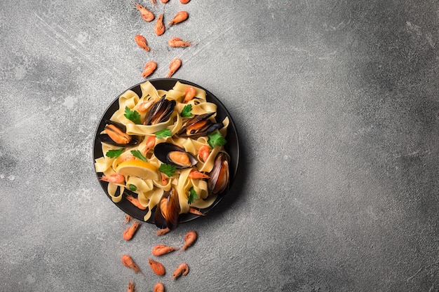 Traditional italian seafood pasta with clams spaghetti alle vongole on stone background with shrimp and mussels. top view