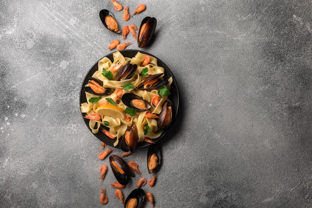 Traditional italian seafood pasta with clams spaghetti alle vongole on stone background with shrimp and mussels