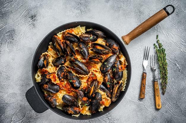 홍합, 스파게티, 토마토 소스를 곁들인 전통 이탈리아 해산물 파스타. 흰 바탕. 평면도.