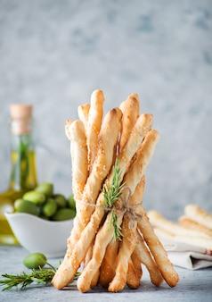 밝은 배경에 올리브 오일과 참깨를 곁들인 전통 이탈리아 스낵 그리시니 브레드스틱, 선별적인 초점