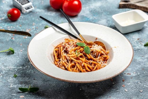 Традиционные итальянские спагетти болоньез с соусом из томатов и мясного фарша, подаются на тарелке с сыром пармезан,