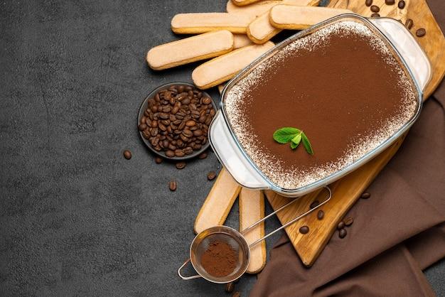 Традиционный итальянский десерт тирамису в стеклянной форме для выпечки на деревянной разделочной доске и печенье савоярди на бетонном фоне или столе