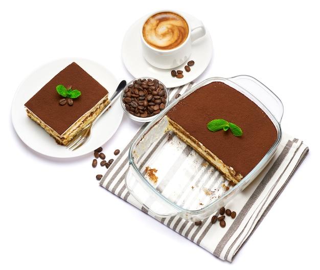 皿の上のガラスのベーキング皿部分と白で隔離されたコーヒーのカップの伝統的なイタリアのティラミスデザート