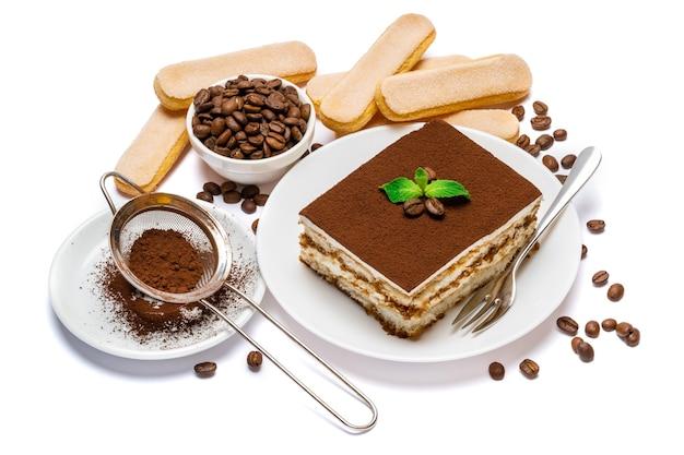 Квадратная часть традиционного итальянского десерта тирамису на керамической тарелке и изолированное печенье савоярди