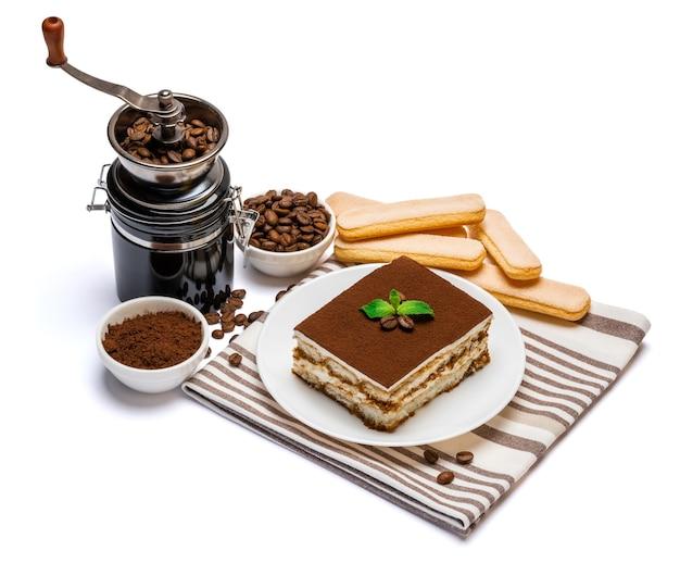 Традиционная итальянская квадратная часть десерта тирамису на керамической тарелке, кофемолке и печенье савоярди изолированно