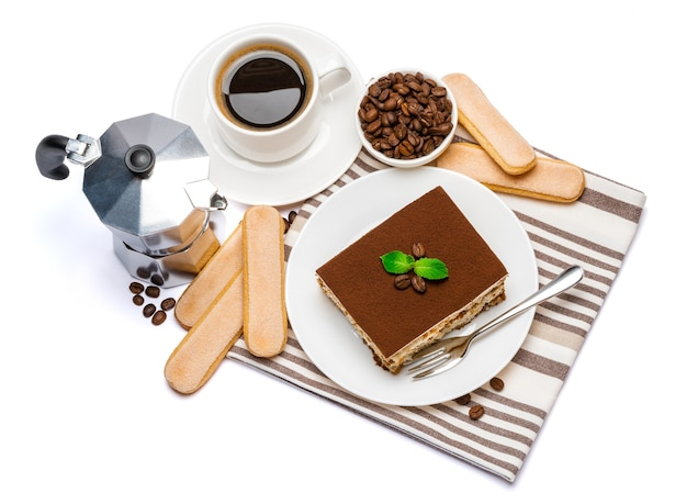 Традиционная итальянская квадратная часть десерта тирамису на керамической тарелке, кофеварка мокко, печенье савоярди и чашка свежего кофе эспрессо изолированы