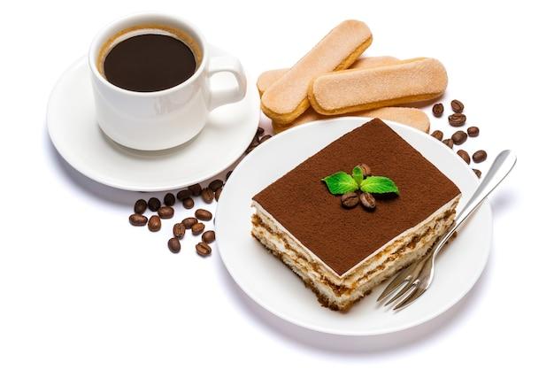 Традиционный итальянский десерт тирамису квадратная часть на керамической тарелке, печенье савоярди и чашка свежего кофе эспрессо изолированы