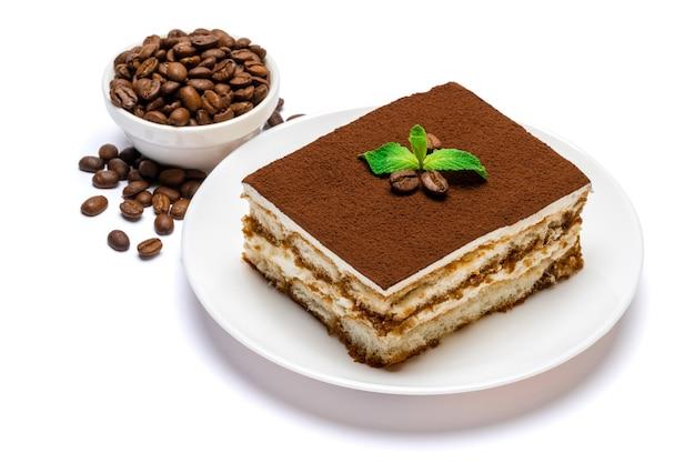セラミックプレートと分離されたコーヒー豆の伝統的なイタリアのティラミスの正方形のデザート部分