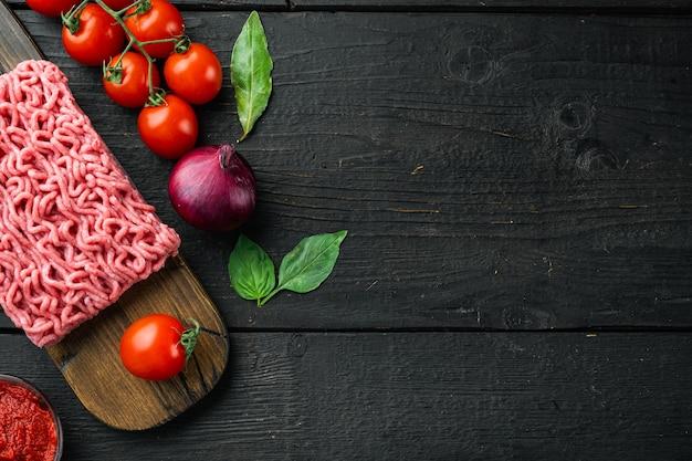 Традиционный итальянский томатный соус болоньезе с ингредиентами, фаршем, помидорами и травами, на деревянной разделочной доске, на черном деревянном столе
