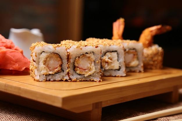 Rotolo di sushi giapponese tradizionale di cucina con riso, gamberetti e crema di formaggio e sesamo su un bordo di legno