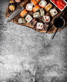 Традиционная японская кухня. суши и роллы. на деревенском столе.