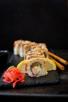 伝統的な日本料理-黒いテーブルに寿司、ロールパン、ソース。