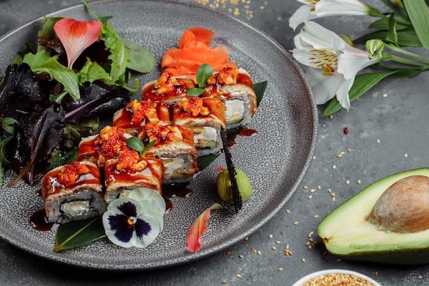 전통적인 일본 음식. 회색 테이블에 장어와 스시 롤.