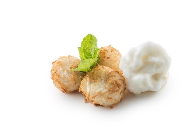 ミントの葉とシャーベットが白で分離された伝統的な日本の揚げ甘いココナッツボール