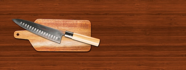 Traditional japanese gyuto chief knife on a cutting board. brown wooden background banner