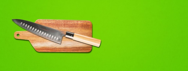 Traditional japanese gyuto chief knife on a cutting board. green banner background