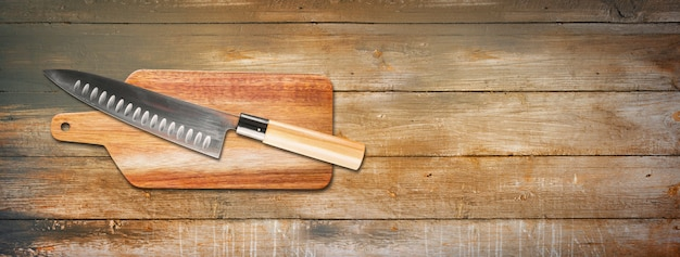 Traditional japanese gyuto chief knife on a cutting board. old wooden background banner