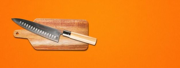 Traditional japanese gyuto chief knife on a cutting board. orange banner background