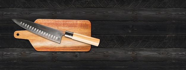 커팅 보드에 전통적인 일본 규토 수석 칼. 검은 나무 배경 배너