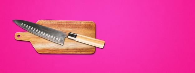 まな板に日本の伝統的な牛刀。ピンクのバナーの背景