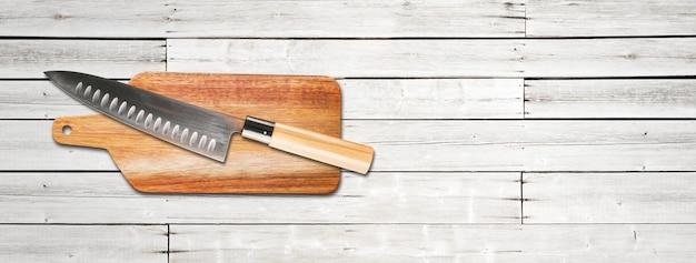 커팅 보드에 전통적인 일본 규토 수석 칼. 흰색 나무 배경 배너