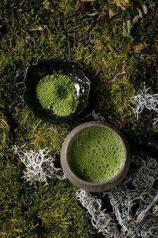 세라믹 컵에 담긴 전통적인 일본의 뜨거운 녹색 거품 차 말과 배경으로 숲 이끼 위에 가루 말. 건강한 천연 음료. 플랫 레이