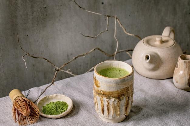 회색 린넨 식탁보에 서 있는 수제 세라믹 컵, 가루 말차, 찻주전자, 대나무 털로 만든 전통적인 일본 뜨거운 녹색 거품 차 말. 건강 음료