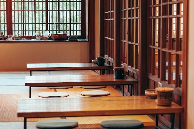 전통적인 일본식 마치야 가옥 또는 나무 테이블과 자연 채광이 들어오는 문이 있는 료칸 레스토랑
