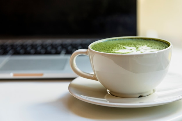 Traditional japanese matcha green tea cup near the laptop on desk